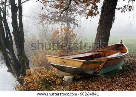 Misty autumn morning by the river with damaged rowboat.