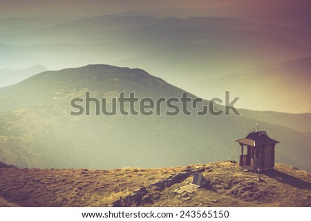 Misty autumn mountain hills landscape. Small chapel with mountains in the background. Filtered image:cross processed vintage effect. - stock photo