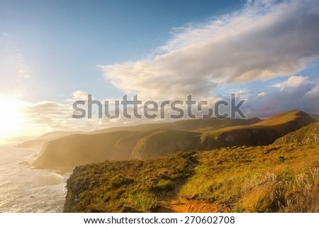 Misty beach in sunset light. Shot on the Otter trail in the Tsitsikamma National Park, Garden Route area, Western Cape, South Africa.  - stock photo