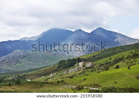 Misty cloud touches the majestic peak of Snowdon, the highest mountain in Wales, set among green Welsh countryside in the valley of Dyffryn Mymbyr, near Capel Curig, Conwy. - stock photo