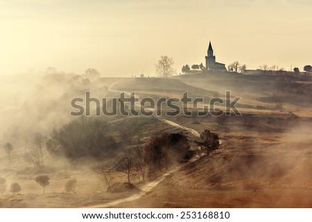 Misty country landscape with church in La Garrotxa, Catalonia - stock photo
