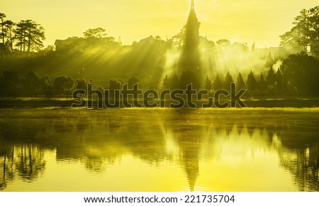 Misty dawn at the lake in spring - stock photo