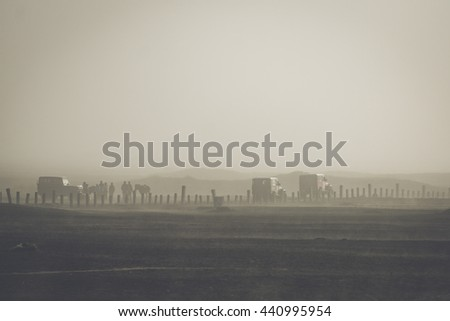 Misty desert landscape with car, horse and man silhouette.