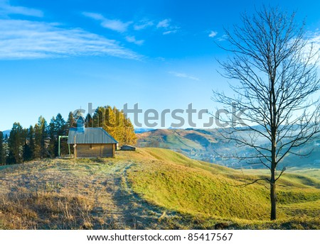Misty early daybreak in autumn  mountain and wooden chapel on mountain top (Jasynja Village, Carpathian ).  Two shots stitch image. - stock photo