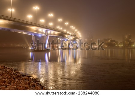 Misty evening scenery with illuminated bridge and ice - stock photo