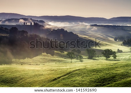 Misty hills and meadows in Tuscany at sunrise - stock photo
