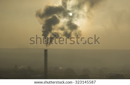 Misty landscape and the sun overshadowed by smoke coming from a pipe