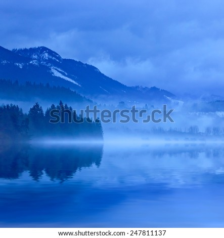 Misty landscape with lake in mountains