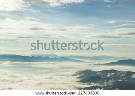 Misty layered mountains in sunrise  - stock photo