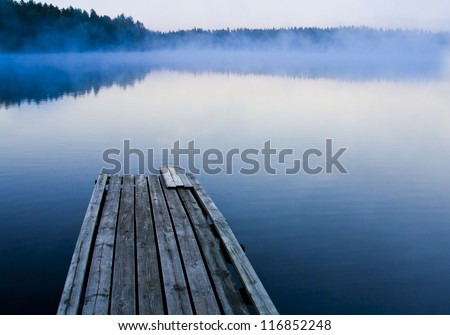 Misty morning and a foggy lake - stock photo