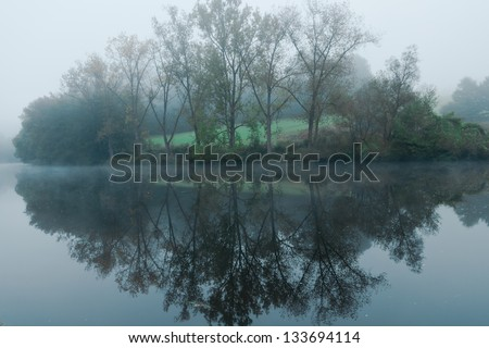 Misty morning lake with tree reflection in water. Foggy landscape with lake in Passau Germany. trees in the mist reflecting on the water - stock photo