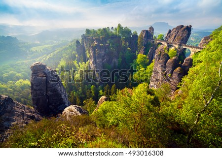 Misty morning on sandstone cliff in Saxony Switzerland with Bastei bridge. Colorful spring scene in Germany, Saxony, Europe. Artistic style post processed photo.