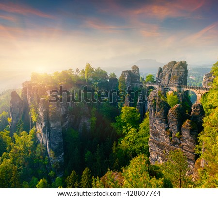 Misty morning on sandstone cliff in Saxony Switzerland with Bastei bridge. Colorful spring sunrise in Germany, Saxony, Europe. Artistic style post processed photo.