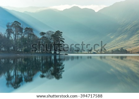 Misty morning with calm reflections of tree's in lake at Buttermere in the Lake District, UK. - stock photo