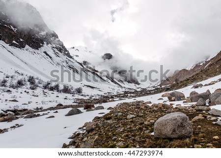misty mountain valley with snow and stones - stock photo
