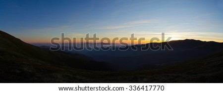 Misty mountains after sunset. panorama - stock photo