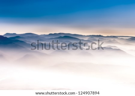 Misty mountains magical landscape view in the autumn with blue sky - stock photo