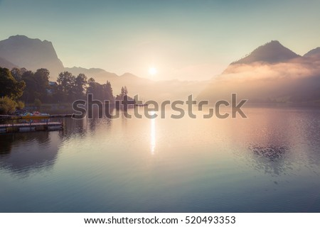 Misty sunrise on Grundlsee lake. Beautiful summer view of Gessl village, Liezen District of Styria, Austria, Alps. Europe. Artistic style post processed photo.