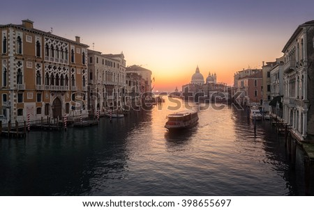 Misty sunrise on the Grand Canal in Venice with a ferry heading away from the Basilica di Santa Maria della Salute