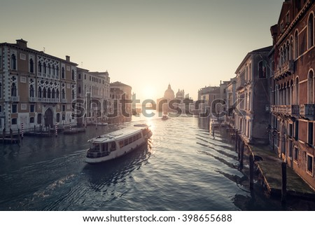 Misty sunrise on the Grand Canal in Venice with a ferry heading towards the Basilica di Santa Maria della Salute