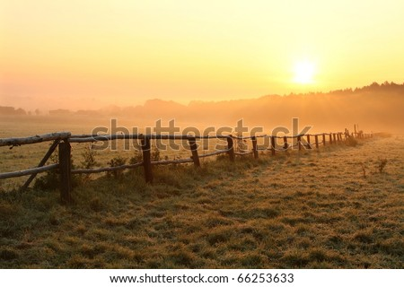 Misty sunrise over grassland with idyllic fence in the foreground.