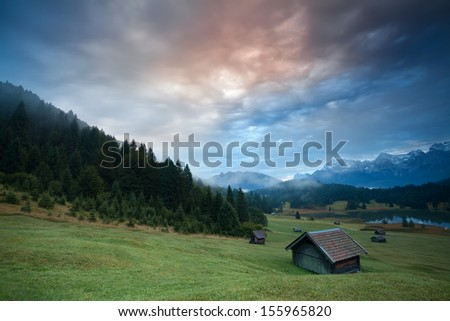 misty sunrise over huts by Geroldsee lake in Bavarian Alps, Germany - stock photo