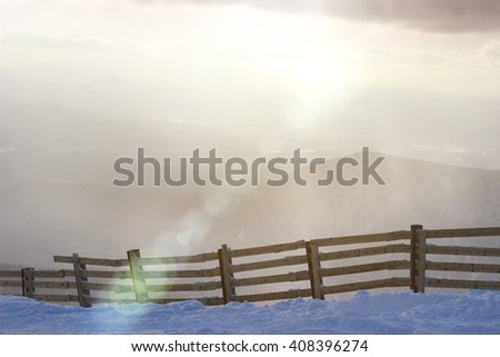Misty sunrise over snowy landscape with idyllic fence in the foreground. - stock photo