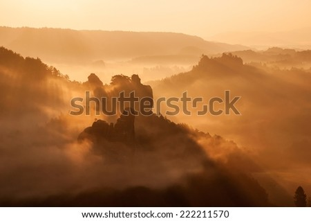 Misty valley during the autumn sunrise with the rocks and the fog below it in national park Saxon Switzerland in Germany - stock photo