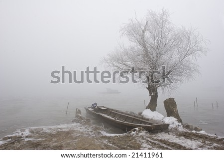 misty view of traditional fishing boats on river Danube mid winter - stock photo