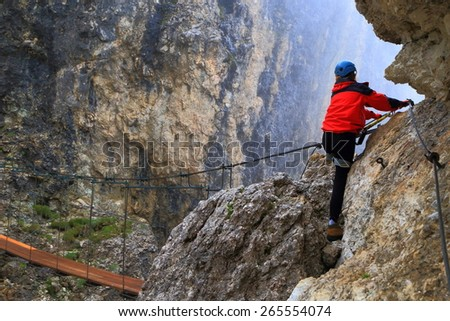 "Misty weather and climber approaching exposed bridge on via ferrata ""Brigata Tridentina"", Sella massif, Dolomite Alps, Italy"