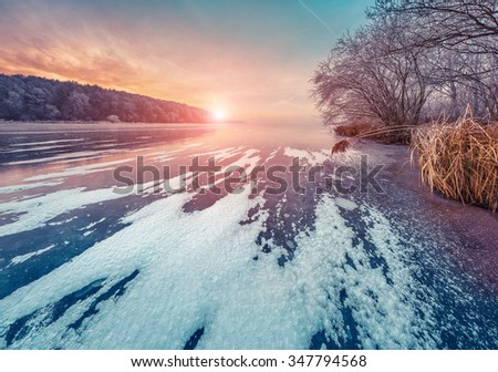 Misty winter sunset on the frozen pond in the city park. Instagram toning. - stock photo