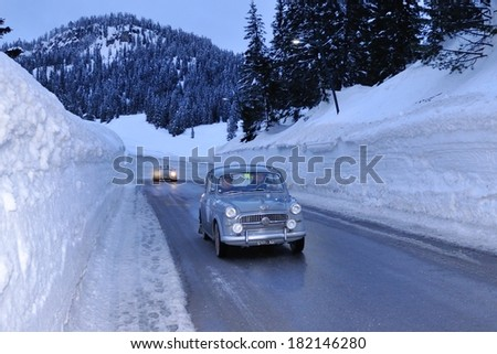 MISURINA, ITALY - FEBRUARY 21: A gray Fiat 1100/103 E takes part to the WinteRace classic car race on February 21, 2014 in Misurina. This car was built in 1957. Some blue cast of the after sunset hour - stock photo