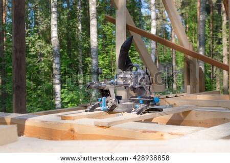 miter saw in building area. tools in wooden house. building ecological house - stock photo