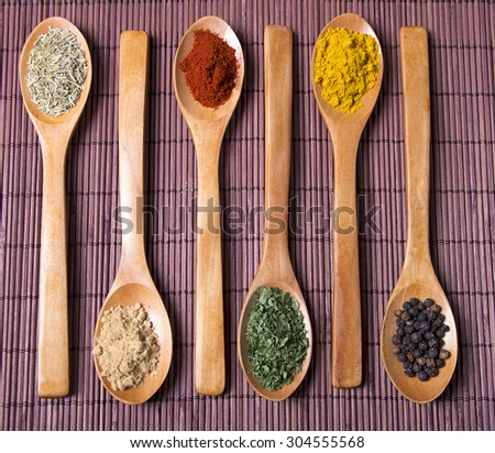 mix aromatic spices on spoons on wooden background  - stock photo