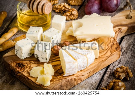 Mix Cheese: Emmental, Camembert, Parmesan, blue cheese, with walnuts and honey on wooden table - stock photo