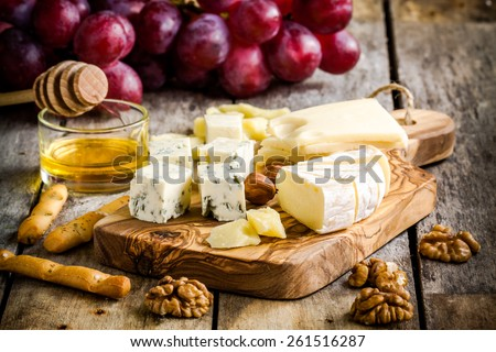 Mix Cheese: Emmental, Camembert, Parmesan, blue cheese, with walnuts, honey and grape on wooden table