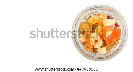 Mix dried fruit pieces in mason jar over white background