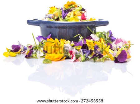 Mix edible flower salad in a blue single pot over white background