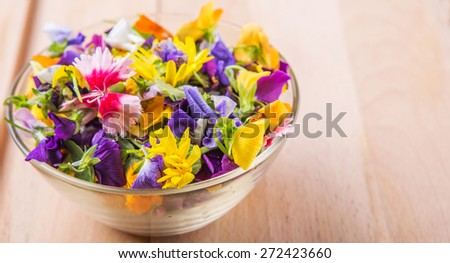 Mix edible flower salad in a glass bowl on wooden cutting board  - stock photo