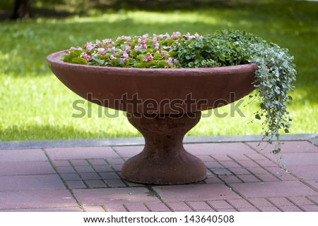 mix flowers in a large vase in the garden - stock photo