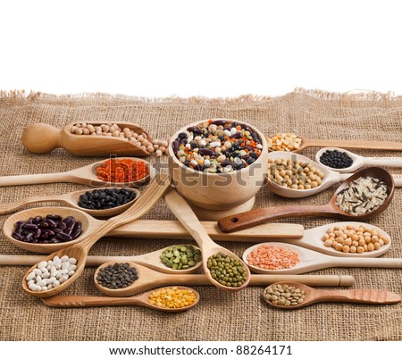 Mix from different beans, legumes, peas, lentils in spoon on the sackcloth - stock photo