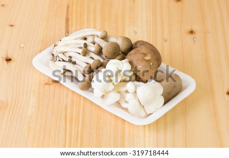 Mix mashrooms in foam plated on wooden - stock photo