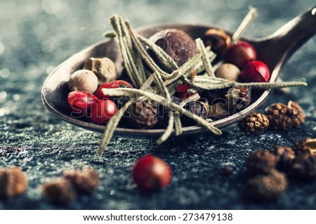 Mix of black, green, red and white peppercorns and rosemary (Schinus molle, Indian Black pepper, Allspice, White Pepper and Green pepper). Selective focus - stock photo