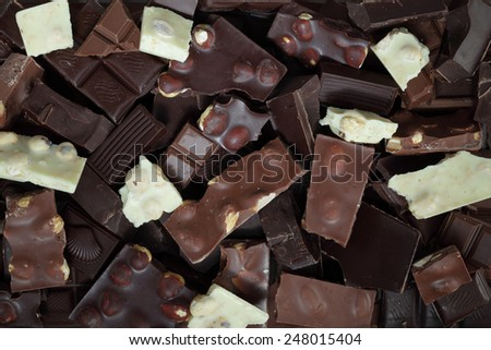 Mix of chocolate bar pieces made of dark chocolate, milk chocolate, white chocolate - stock photo