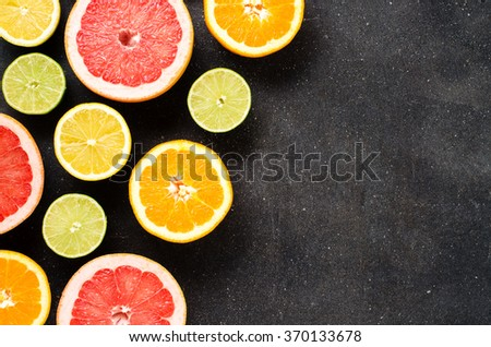 Mix of citrus fruits on dark table - stock photo
