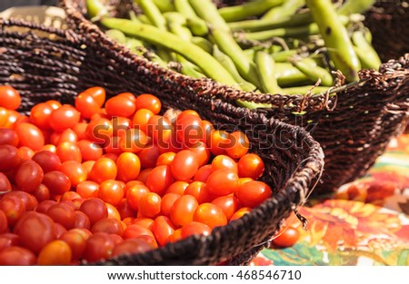Mix of colorful cherry tomatoes and string beans grown and harvested in Southern California and displayed at a farmers market.