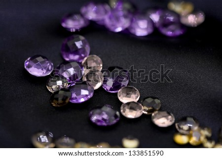 Mix of colorful faceted gems on black background - stock photo