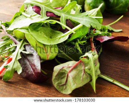 Mix of different kinds of greens on the wooden background. Shallow dof. - stock photo