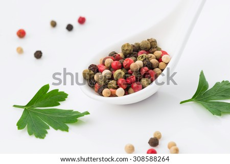 mix of different peppers in a white ceramic spoon, mixture of hot pepper, red pepper, black pepper, white pepper, green pepper on a white  background - stock photo