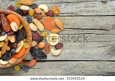 Mix of dried fruits and nuts  in a wooden bowl on wooden table - symbols of judaic holiday Tu Bishvat. Copyspace background.Top view. - stock photo